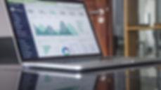 Počítač s grafy a tabulkami na stole