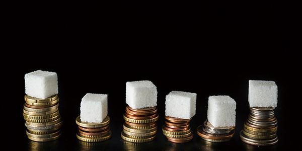 積み上げられたコインの上に角砂糖を載せて「砂糖税」をイメージした写真|副腎疲労HP