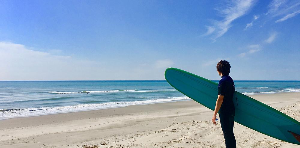 ロングボードを持って海を見ている男性 副腎疲労HP
