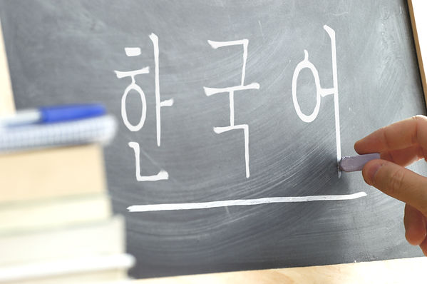 Hand writing on a blackboard in a Korean