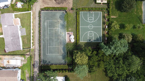 Full court basketball next to clay tennis court