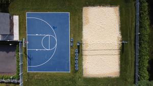 Half basketball court next to sand volleyball court