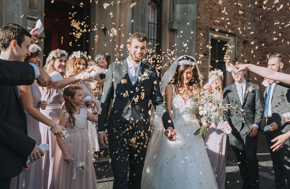 Newly married couple are showered with biodegradable confetti by their family and friends. The bride carries a botanical bouquet designed by Emma Jane Floral Design.