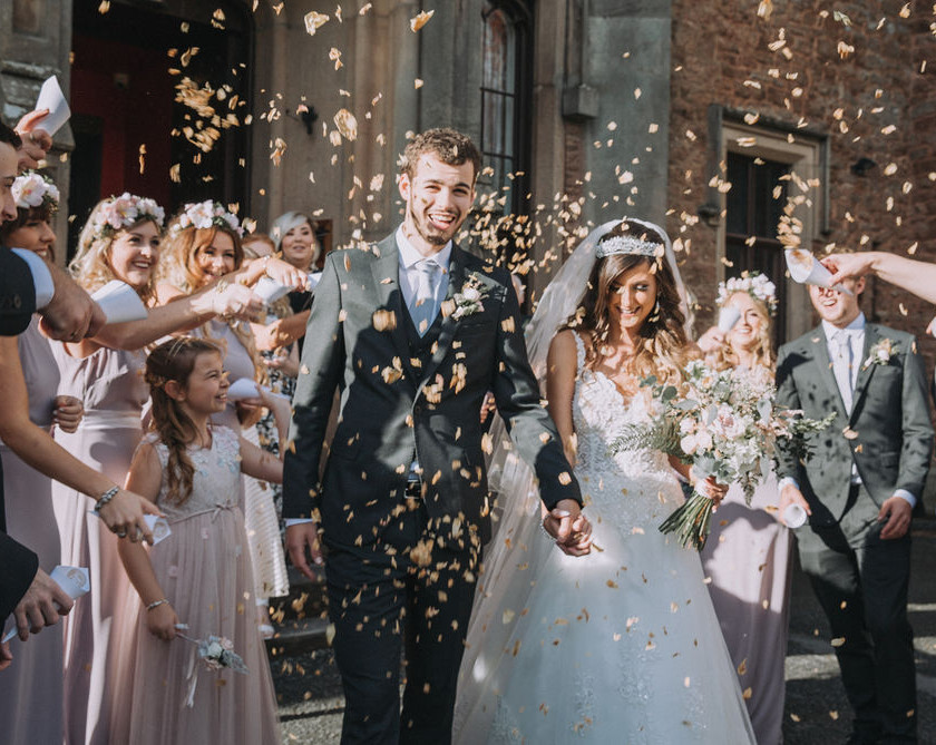 Bride and groom enjoy their confetti moment using air dried biodegradable ecofriendly rose petal confetti from welshpool wedding florist emma jane floral design