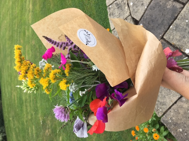 Emma jane floral design picks hand grown blooms from the garden and wraps in brown kraft paper with logo sticker