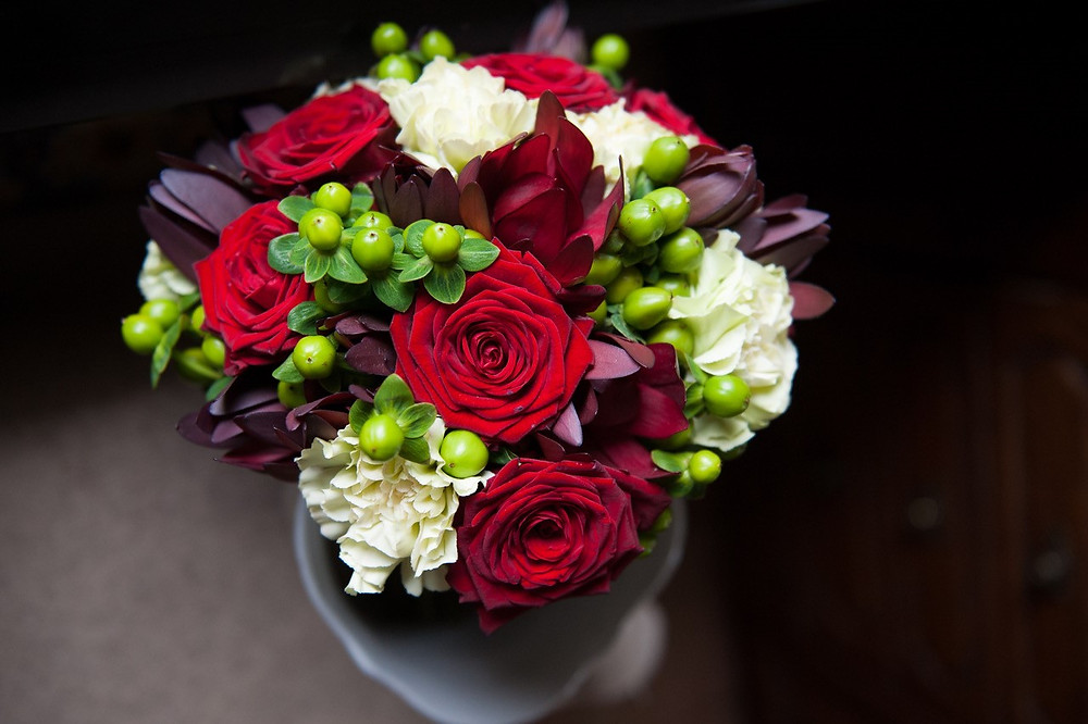 Red and white bridal bouquet with green berries