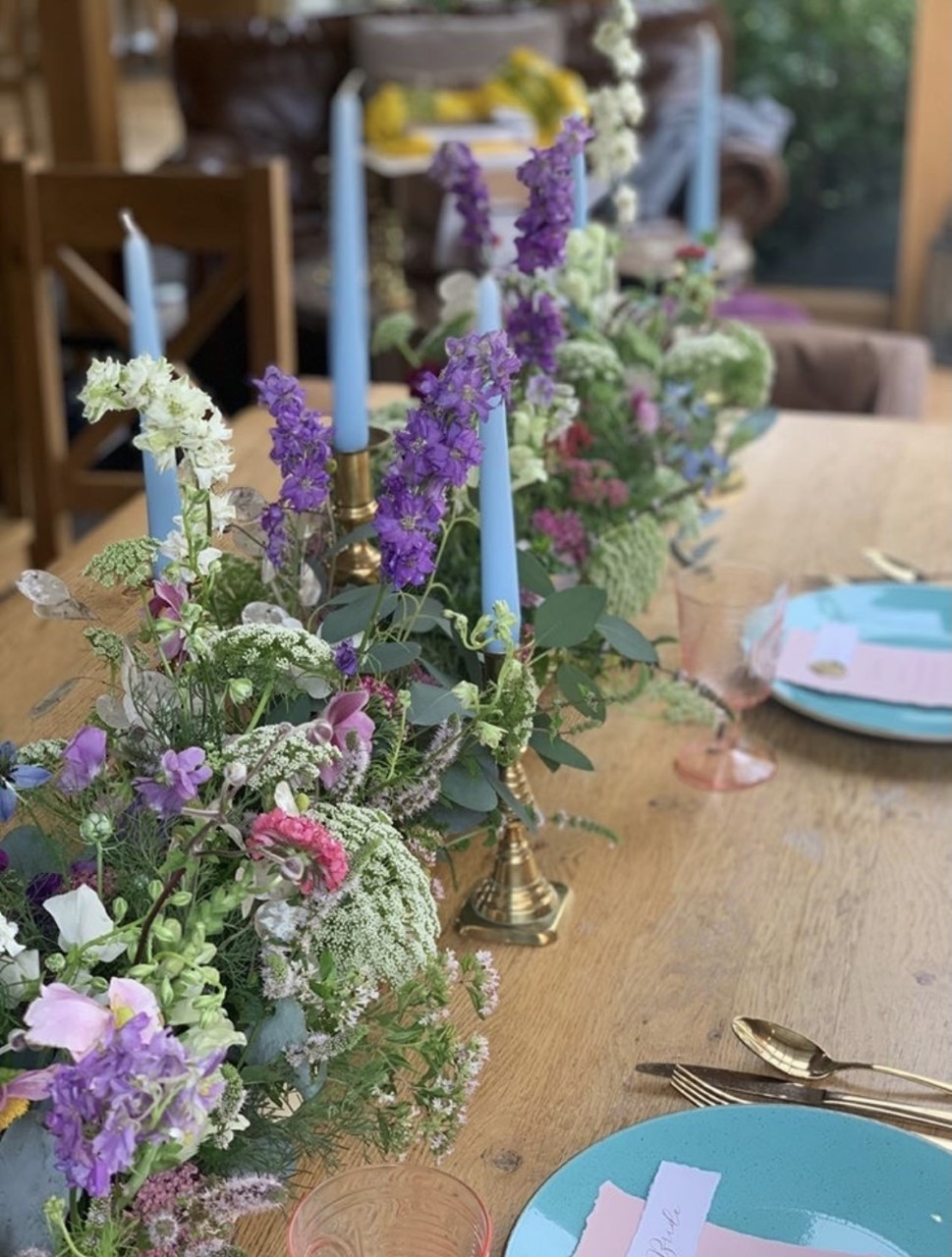 Floral meadow table runner incorporating purple and blue flowers sits on a table with blue candles in antique brass holders and blue tableware with gold cutlery. Set up ready for a wedding breakfast. Wedding flowers by Emma Jane Floral Design.