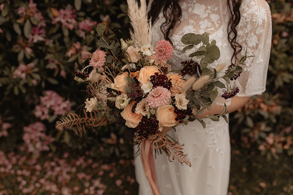 Bride holding boho bouquet of peach roses, pampas and bunny tail grasses standing in front of a floral background. Bouquet by Emma Jane Floral Design.