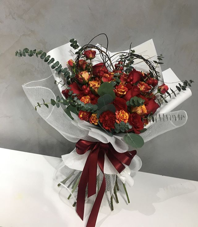 Emma Jane Floral Design creates a luxury heart shaped hand tied bouquet using blooms in shades of red and orange, tied in the korean floral style.