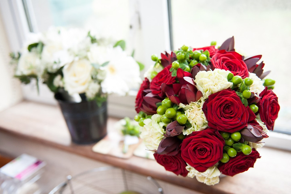 Red and white bridal bouquet with green berries sitting on a window sill next to white flowers in a black pot.