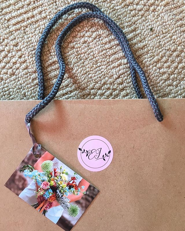 Emma Jane Floral Design lays out a brown kraft bag with logo sticker and business card