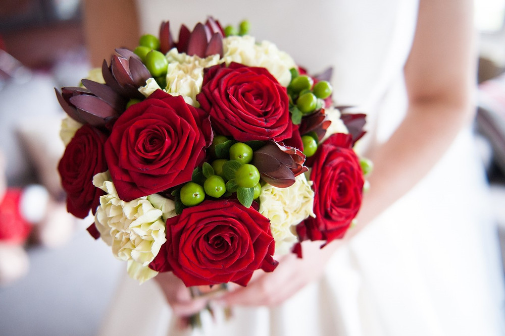 Red and white bridal bouquet with green berries.
