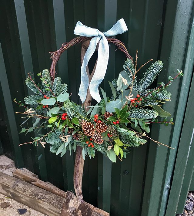 Emma Jane Floral Design creats a luxury biodegradable plastic foam free christmas wreath including seasonal holly, pine cones and tied with natural hessian ribbon
