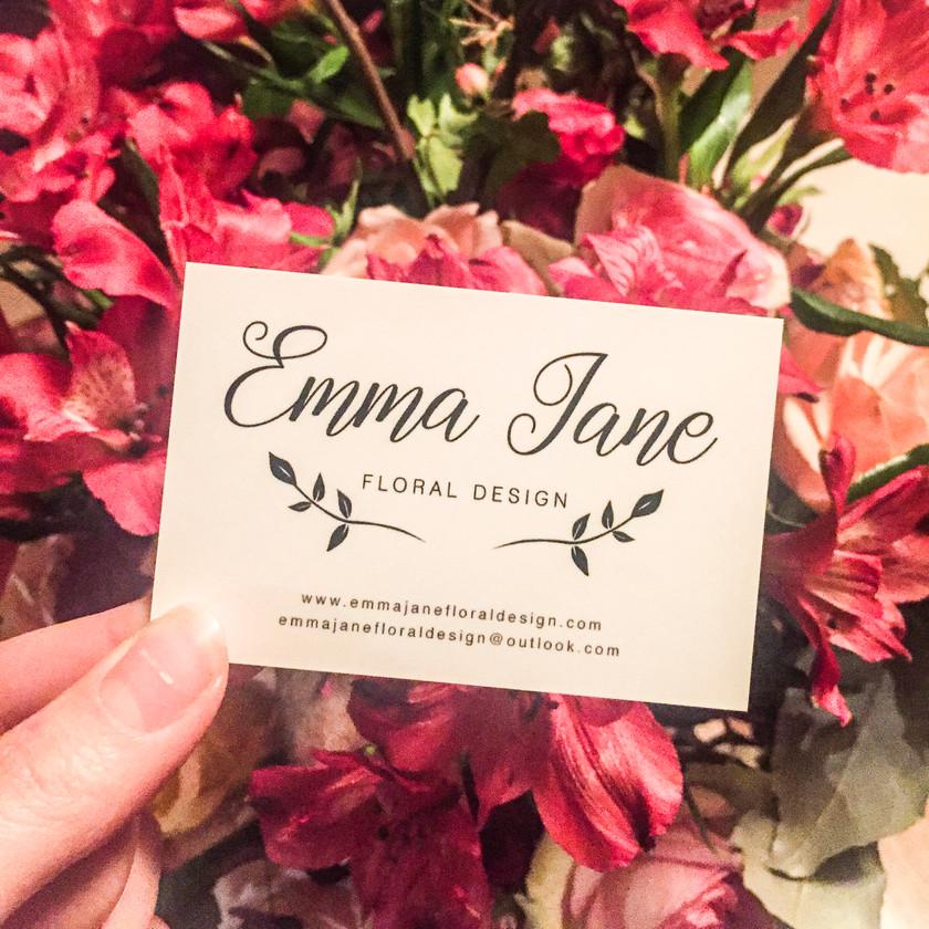 Emma Jane Floral Design logo business card in front of pink bloom flowers