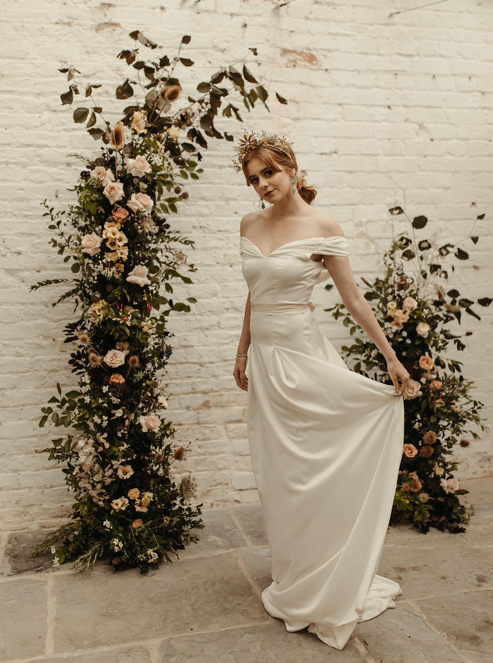 Bride in crown headdress stands in front of a floral installation display by Emma Jane Floral Design.