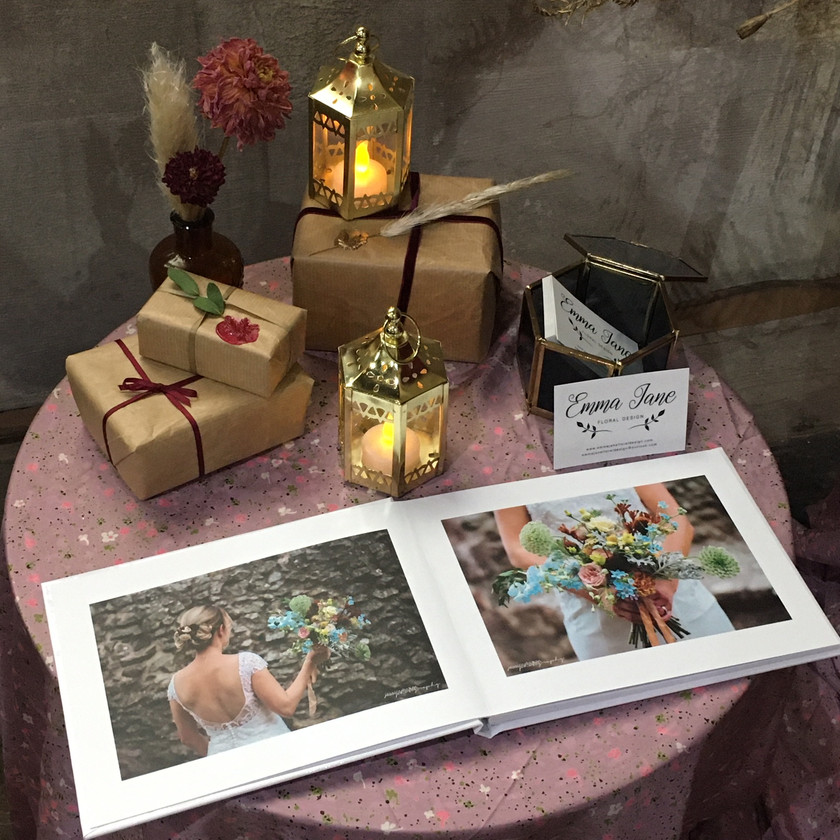 Emma jane floral design display table with photo book lanterns and presents wrapped in kraft paper with wax seal stamps