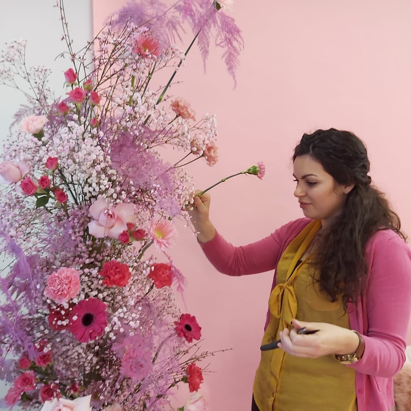 Florist in a yellow and pink top positions a pink carnation in a large floral installation by emma jane floral design