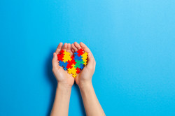 Child hand holding colorful heart on blu