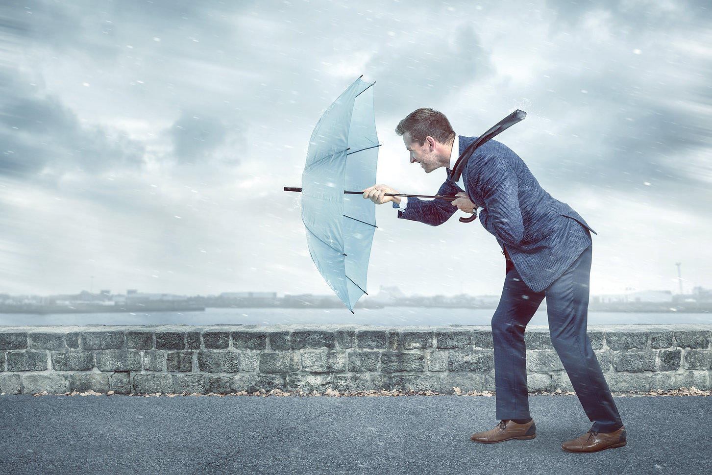 Businessman with an umbrella is facing s