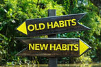 Old Habits - New Habits signpost with fo