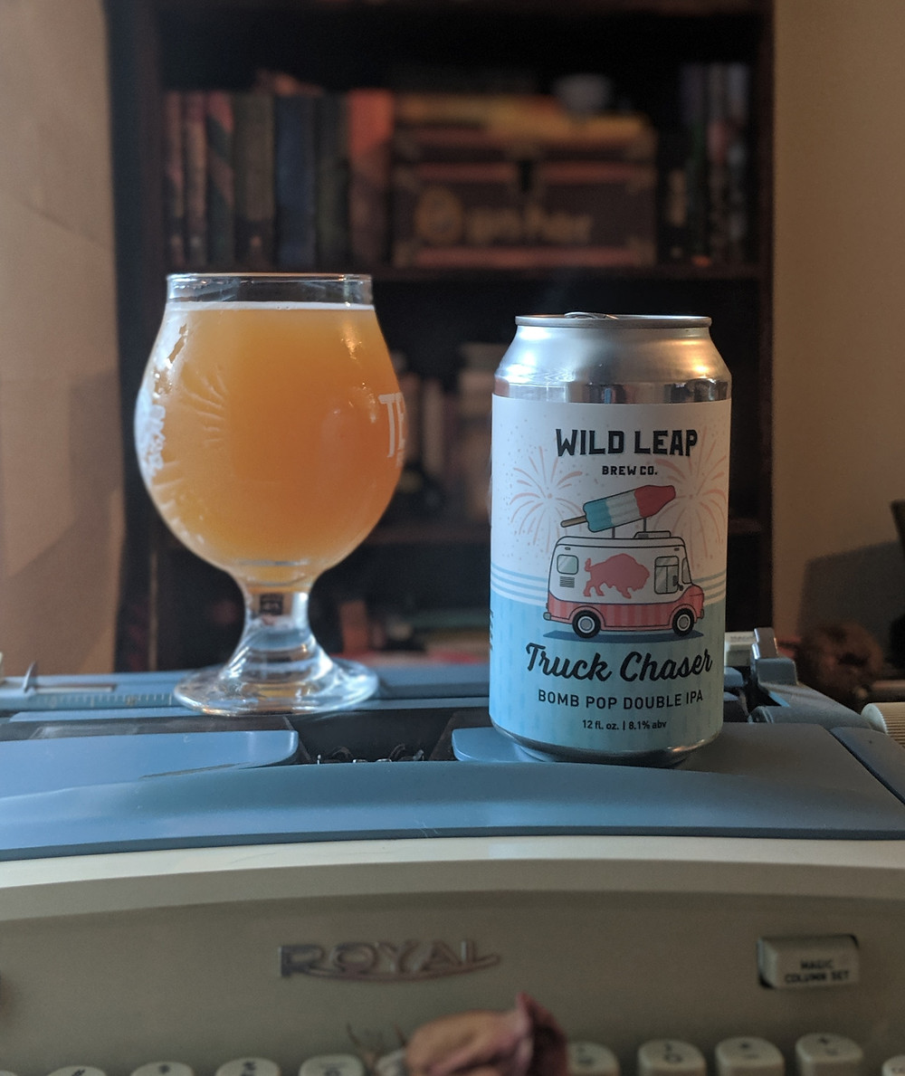 Beer can and glass sitting on typewriter