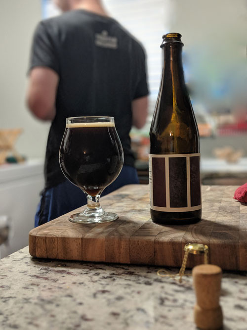 Beer bottle with glass holding dark brown beer