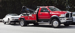 Red tow truck towing a white car