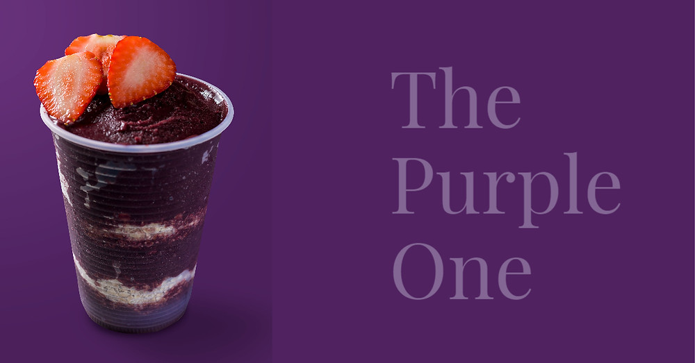 purple smoothie in a cup with halved strawberries resting on top