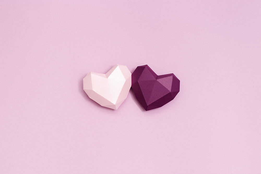 Two 3D hearts close together on colourful background