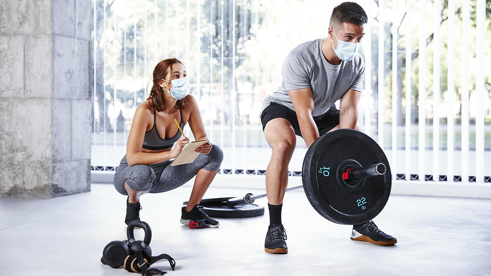 Female-personal-trainer-male-training-with-weights-wearing-masks