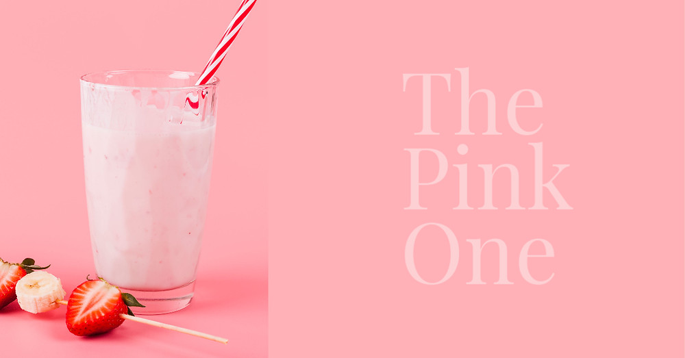 pink smoothie in a glass with stripy red and white straw and strawberry and banana kebab