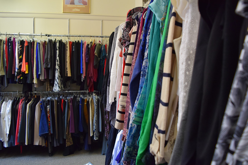 Racks of clothes are lined up against a wall.