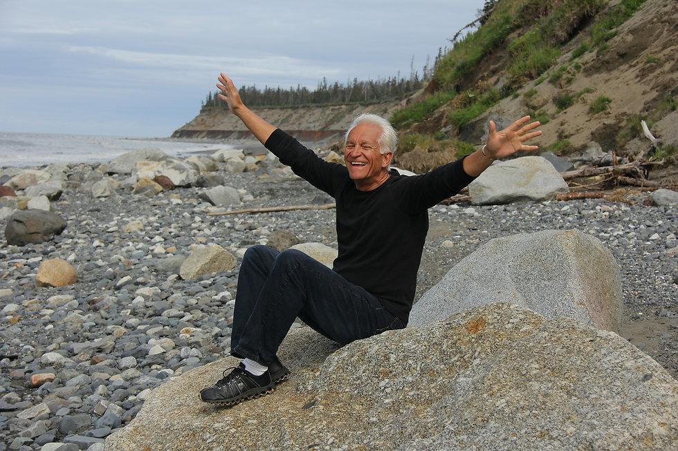 man smiles on rocky shore.jpg