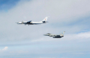 An RAF Typhoon flys alongside a Russian bomber jet in a blue and cloudy sky