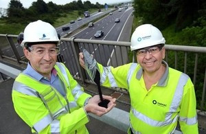 Martin Bolt, left, of Highways England and Paul Fleetham of Tarmac above the M1 in the East Midlands with some of the rubber granules being trialled in the road surface