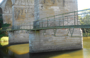 The soon-to-be refurbished, suspended footbridge hangs across three of the arches of the Roxburgh (Teviot) Viaduct