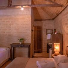 Cada suíte tem uma cama de casal e podemos acrescentar uma de solteiro. Tem frigobar, ventilador e aparador de madeira, além de varanda com rede.