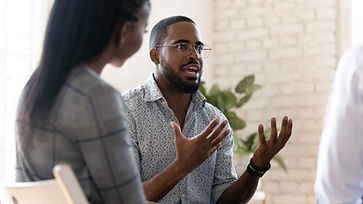 Head shot young african american male psychologist meeting patients at group therapy. Seri