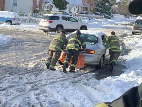FSMFD Members assist a car stuck in the snow