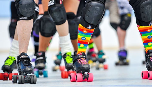 Close up of several skater's legs wearing roller skates, colourful socks and knee pads