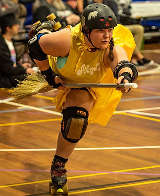 Skater dressed in yellow skating one foot holding a broom as if flying.