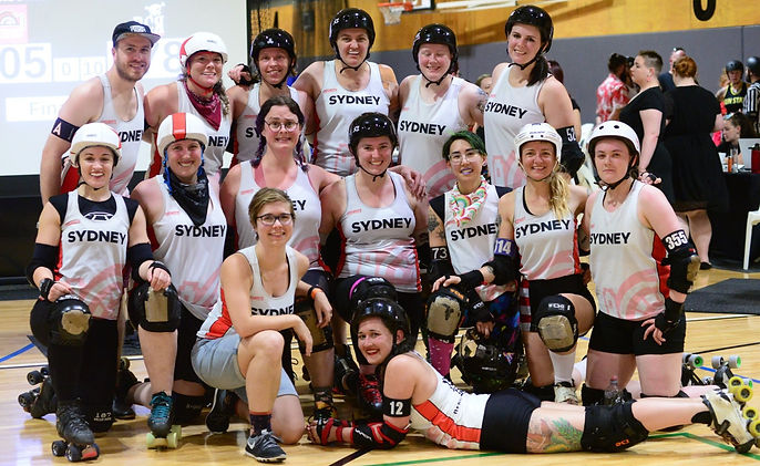 15 Smiling Assassins pose for a photo after a game wearing white Sydney Roller Derby League uniforms and derby gear