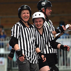 2 Referees wearing stripes and protective gear smile for the camera