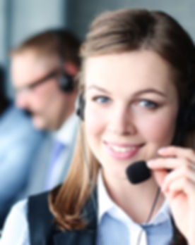Portrait of call center worker accompanied by her team.jpg Smiling customer support operator at work