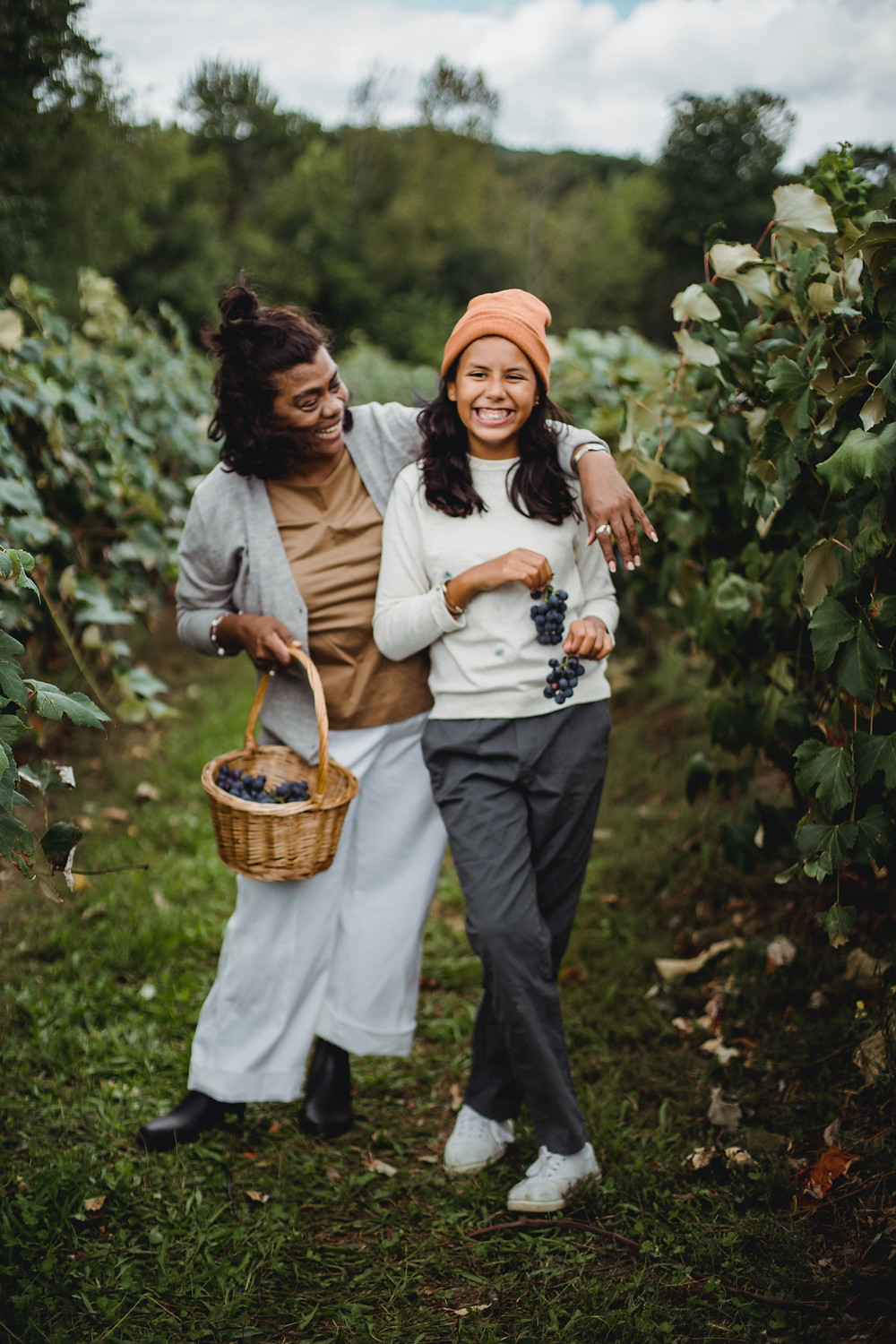 Mother and daughter in vineyard with grapes