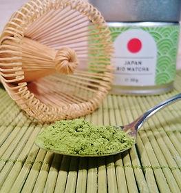 Teelöffel mit Matcha-Pulver, Bambusbesen und Matcha-Dose.