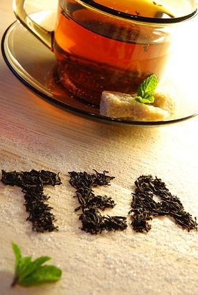 """Teeglas. Im Vordergrund ist aus Teeblättern das Wort """"TEA"""" gelegt."""