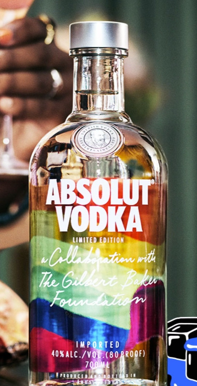 """Absolut Vodka bottle with the Pride flag on the label and the script, """"A Collaboration with The Gilbert Baker Foundation."""" The bottle sits on a table. Someone is holding a drink behind it."""