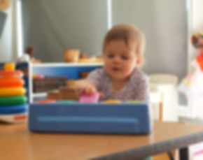 An infant playing with a pop-up toy