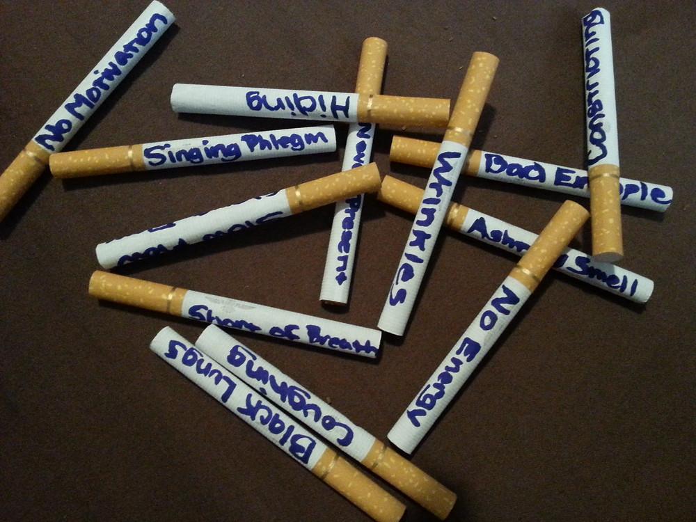 Cigarette smoking symptoms written on cigarettes